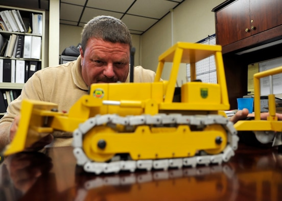 Richard Turner, a forest technician assigned to the 325th Civil Engineer Squadron Natural Resources, inspects a home-made wooden toy at the Natural Resources building June 14, 2016. Turner was chosen as the 'Unsung Hero' as part of Tyndall Air Force Base's squadron of the week program, and one of his hobbies includes woodworking. (U.S. Air Force photo by Senior Airman Sergio A. Gamboa/Released)