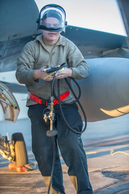 Airman 1st Class Ryan Bateman, a 354th Aircraft Maintenance Squadron assistant dedicated crew chief, tops off the air in the tire of an F-16 Fighting Falcon fighter aircraft flown by the 18th Aggressor Squadron (18th AGRS) while working swing shift June 14, 2016, during RED FLAG-Alaska (RF-A) 16-2 at Eielson Air Force Base, Alaska. The 18th AGRS supports RF-A by sharing its knowledge of flying to participating units and ensuring the U.S. and its allies receive the best air combat training possible. (U.S. Air Force photo by Staff Sgt. Shawn Nickel/Released)