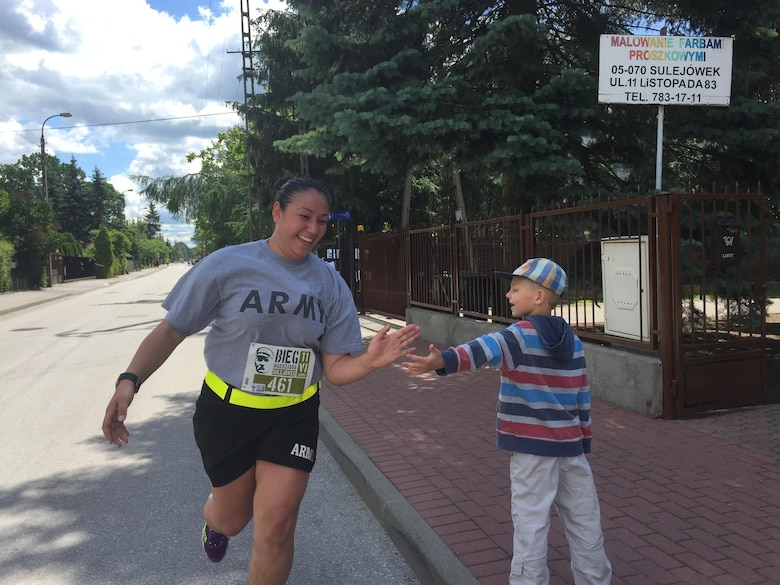 U.S. Army Reserve Sgt. Jennifer Hoeppner, a human resource specialist with the 364th Expeditionary Sustainment Command Marysville, Washington high fives a young Polish resident during a 10-kilometer race in Sulejowek, Poland.  The 364th is participating in Anakonda 16, a Polish-led national event that seeks to train, exercise and integrate Polish national command and force structures into an Allied, joint, multinational environment. (Photo by Capt. A. Sean Taylor, 649th RSG)