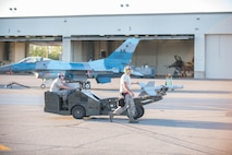 U.S. Air Force Staff Sgt. Nathan Mendoza escorts Airman 1st Class Tyler Lounds, both aircraft armament systems technicians from the 354th Maintenance Squadron, as Tyler drives the MJU-1 Jammer munition vehicle on the way to an F-16 Fighting Falcon fighter aircraft while working swing shift June 14, 2016, during RED FLAG-Alaska (RF-A) 16-2 at Eielson Air Force Base, Alaska. Jets are flown almost double the normal hours during RF-A, increasing the need for maintenance, which provides training for support personnel in sustainment of large-force deployed air operations. (U.S. Air Force photo by Staff Sgt. Shawn Nickel/Released)