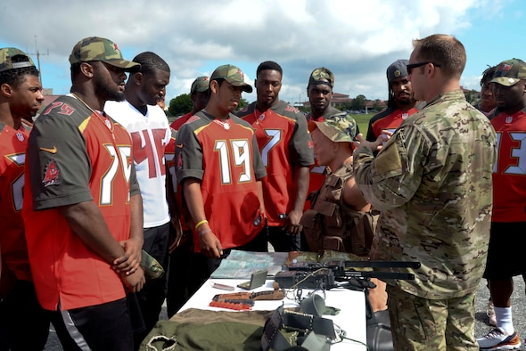 (Right) Staff Sgt. Benjamin Heard, Survival, Evasion, Resistance and Escape specialist, explains the use of survival tools to rookies of the Tampa Bay Buccaneers at MacDill Air Force Base, Fla. June 10, 2016. The rookies received the opportunity to test equipment, learn basic survival skills and sample food rations.