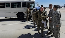 Airmen from the 66th Rescue Squadron and 823rd Air Maintenance Squadron shake the hands as they disembark from a bus after returning from deployment at Nellis Air Force Base, Nev., June 7. The deployment began approximately four months ago as members of the 823rd MXS and 66th RQS traveled to Afghanistan. (U.S. Air Force photo by Airman 1st Class Kevin Tanenbaum)