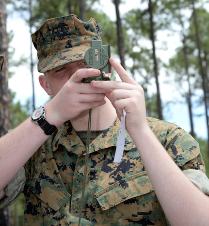 A Marine Corps Junior Reserve Officers Training Corps cadet from Plaquemine High School, Plaquemine, La., puts his compass and map reading skills to test while navigating the Land Navigation Course during a Cadet Leadership Camp aboard Marine Corps Logistics Base Albany, June 8.