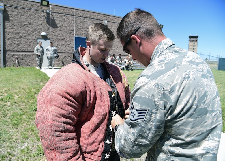 Cadet John Parks, U.S. Air Force Academy, puts on a protective bite suit with the help of Staff Sgt. John Cooper, 460th Security Forces Squadron military working dog handler, before a MWD demonstration June 15, 2016, at Buckley Air Force Base, Colo. The cadets toured Buckley's units and missions, while engaging with leaders of all ranks in order to gain a better understanding of an operational air force base. (U.S. Air Force photo by Tech. Sgt. Nicholas Rau)