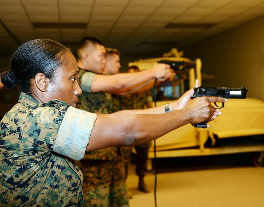 Marines use Marine Corps Logistics Base Albany's Indoor Simulated Marksmanship Trainer to help familiarize themselves with weapons before qualifying on the pistol range, recently.