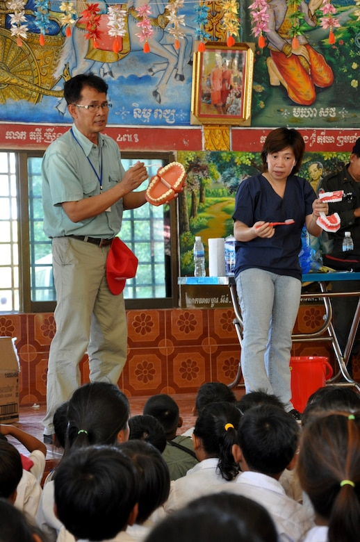 Minh Huong, the lead for the East Meets West - Dental non-governmental organization based in Vietnam, speaks to a group of children on the importance of dental hygiene while Mam Sochenda, a translator for Pacific Angel 16-2 translates her words, June 15, 2016, in Kampot Province, Cambodia. Dental providers from East Meets West, a non-governmental organization based in Vietnam, partnered with U.S., Cambodian, Australian, Vietnamese and Thai military counterparts as part of Pacific Angel 16-2, a multilateral humanitarian assistance/civil military mission, to provide the multitude of children basic dental examinations and, more importantly, educate them on the importance of proper dental hygiene. (U.S. Air Force photo by Capt. Susan Harrington/Released)