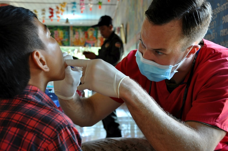 U.S. Navy Lieutenant Matthew Kanter examines a young Cambodian boy during a dental hygiene outreach event for Angchhum Trapeang Chhouk School in Kampot Province, Cambodia, June 15, 2016. Approximately 187 children from the school received oral hygiene education and fluoride treatments along with a toothbrush and toothpaste to take home as part of Pacific Angel 16-2. Pacific Angel includes general health, dental, optometry, pediatrics, physical therapy and engineering programs as well as various humanitarian aid and disaster relief subject matter expert exchanges. The mission enhances participating nations' humanitarian assistance and disaster relief capabilities while providing needed services to people throughout the region. Kanter is a U.S. Navy dentist deployed from Marine Corps Air Station Miramar. (U.S. Air Force photo by Capt. Susan Harrington/Released)