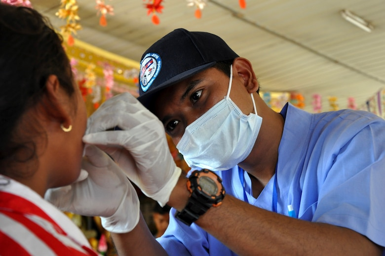Phon Pagna, a dental administrator for East Meets West non-governmental organization examines a young Cambodian girl from Angchhum Trapeang Chhouk School in Kampot Province, Cambodia, June 15, 2016, as part of a dental hygiene outreach event during Pacific Angel 16-2. Approximately 187 children from the school attended the event and received oral hygiene education and fluoride treatments. The oral hygiene education day was planned by East Meets West NGO in partnership with the Kampot Provincial Health Clinic, but executed by both U.S., Australian and Cambodian dentists and volunteers, further building on the relationships formed throughout the Pacific Angel 16-2 mission. (U.S. Air Force photo by Capt. Susan Harrington/Released)