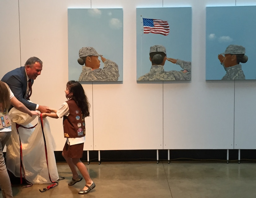 "Artist Steve Alpert thanks a Brownie Scout for helping him unveil the triptych ""Portrait of a Woman"" at the Women in Military Service for America Memorial located at the entrance of Arlington National Cemetery, Va., June 13, 2016. DoD photo by Jim Garamone"