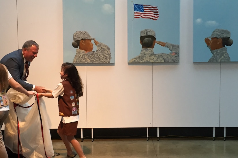 """Artist Steve Alpert thanks a Brownie Scout for helping him unveil the triptych """"Portrait of a Woman"""" at the Women in Military Service for America Memorial located at the entrance of Arlington National Cemetery, Va., June 13, 2016. DoD photo by Jim Garamone"""