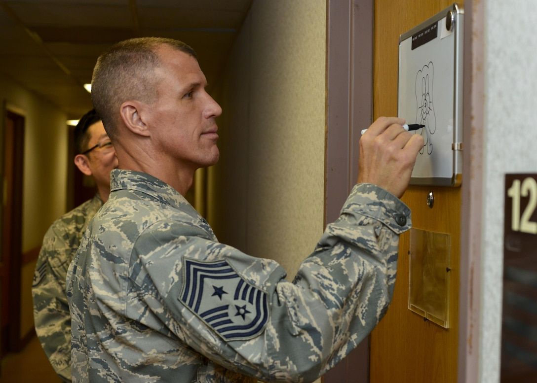 Chief Master Sgt. Steve McDonald, Air Combat Command command chief, draws a picture on a 694th Intelligence Surveillance and Reconnaissance Group Airman's dormitory door at Osan Air Base, Republic of Korea, June 16, 2016. Part of McDonald's visit to Osan included a tour of one of the 694th IRSG's dorms to see the living conditions of its Airmen. (U.S. Air Force photo by Senior Airman Victor J. Caputo/Released)