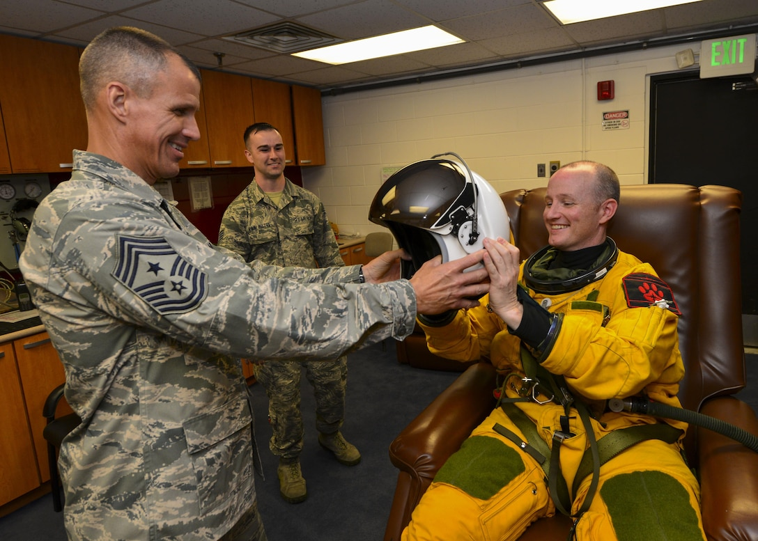 Chief Master Sgt. Steve McDonald, Air Combat Command command chief, hands a helmet to Lt. Col. Todd Larsen, 5th Reconnaissance Squadron commander, during preflight preparations at Osan Air Base, Republic of Korea, June 16, 2016. McDonald toured several geographically-separated ACC units at Osan, including the 5th RS, which is part of the 9th Reconnaissance Wing at Beale Air Force Base, Calif. (U.S. Air Force photo by Senior Airman Victor J. Caputo/Released)