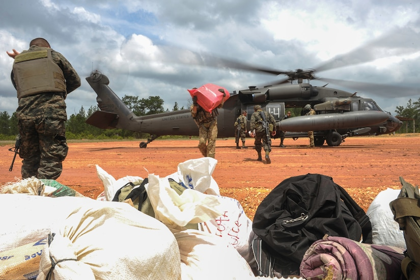 Honduran military members download supplies from a UH-60 Black Hawk helicopter during the twentieth iteration of Operation CARAVANA, in Mocorón, Honduras, June 8, 2016. Joint Task Force-Bravo's 1st Battalion, 228th Aviation Regiment provided two Black Hawks and two CH-47 Chinooks for the troop transport, in addition to Honduran Air Force UH-1 Hueys. In the past, the Honduran military relied primarily on logistic ships to transport the personnel and supplies, making multiple stops throughout the coastal region before dropping off the troops and returning to home port. The whole process took more than a week, whereas transporting by helicopter takes only a few hours and allows access to even more remote areas. (U.S. Air Force photo by Staff Sgt. Siuta B. Ika)