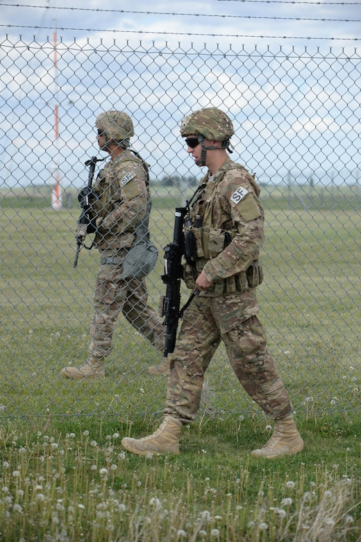U.S. Air Force members from right to left Airman 1st Class Tyler Ibach and Staff Sgt. Aaron Keith, both of the 219th Security Forces Squadron, do a routine check around a Minot Air Force Base, missile alert facility, near Minot, North Dakota, May 24, 2016. They are two of the North Dakota Air National Guard members who took primary positions for missile filed security in an entire 'sector' of the missile field complex during a two week period from May 23 through June 4. This is the fourth time such an annual training surge has happened with the 219th SFS in the complex, which covers 8,500 square miles over the North Dakota plains near Minot and includes dozens of missile field alert facilities and missile launch facilities. (U.S. Air National Guard Photo by Senior Master Sgt. David H. Lipp/Released)
