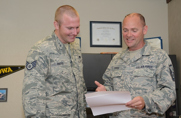 185th Air Refueling Wing, Iowa Air National Guard base education and training manager Master Sgt. Larry Carda looks at a Community College of the Air Force progress report with Staff Sgt. Wes Rueter in Sioux City, Iowa on June 16, 2016. The Community College of the Air Force ranked the Iowa Air National Guard number one in CCAF degrees awarded in the past year. (U.S. Air National Guard photo by Master Sgt. Vincent De Groot)