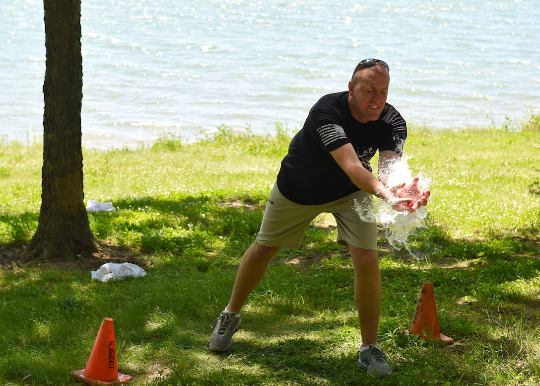 Tech. Sgt. Matthew Flowers, a targeteer with the 132nd Intelligence Surveillance and Reconnaissance Group, attemps to catch a water balloon, June 6, 2016, at Moffitt Resevoir Park in Cumming, Iowa. The ISRG held an amazing race event to kickstart Annual Training Week. (U.S. Air National Guard photo by Staff Sgt. Michael J. Kelly/Released)