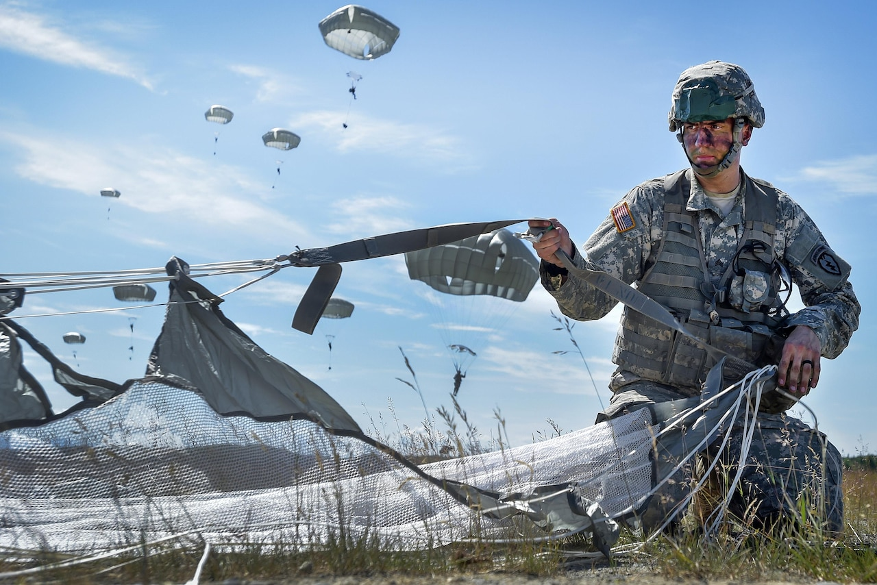 Army Sgt. John Arriaga recovers his parachute after participating in an airborne proficiency operation during Exercise Arctic Aurora at Joint Base Elmendorf-Richardson, Alaska, June 9, 2016. Arriaga is assigned to the 25th Infantry Division's Company B, 3rd Battalion, 509th Parachute Infantry Regiment, 4th Infantry Brigade Combat Team (Airborne). Air Force photo by Justin Connaher