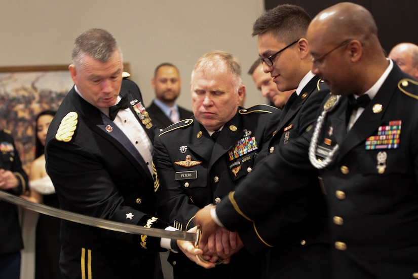 The Army's birthday was observed with a cake-cutting ceremony by the youngest Soldier present (Pfc. Giovani Hernandez - 3rd person) and by the oldest (Master Sgt. Steven Peters - 2nd person), assisted by 76th ORC Commander, Maj. Gen. Ricky L. Waddell (1st person) and Command Sgt. Maj. Michael J. Robinson (4th person), during the 76th ORC's Utah Army Ball, June 11, at the Living Planet Aquarium, Salt Lake City.