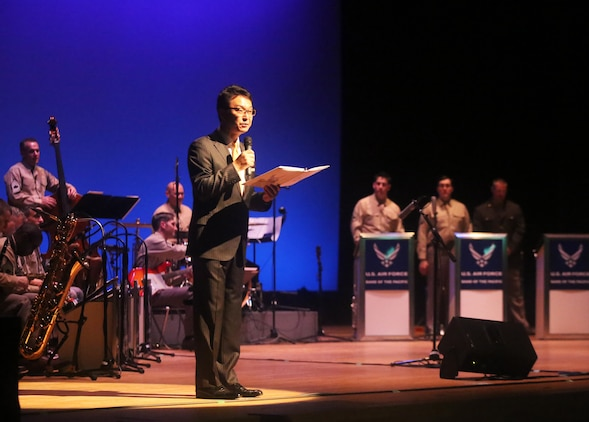 Masato Yagi. community relations specialist gives opening remarks to the audience before U.S. Airmen with the U.S. Air Force Band of the Pacific-Asia Showcase jazz ensemble perform at the Iwakuni Civic Hall in Iwakuni, Japan, June 16, 2016. The band of the Pacific-Asia consists of 24 active-duty professional musicians who showcase their talents throughout the Western-Pacific region in support of military and community relations objectives. Based out of Yokota Air Base, Japan, The Pacific Air Force band was established as the United States Air Force Band of the Pacific at Eglin Field, Florida, in 1941. It is one of 12 U.S. Air Force bands, to include the 15-member detachment group stationed at Joint Base Pearl Harbor-Hickam, Hawaii. Pacific Trends and other protocol groups also perform with the Pacific Air Force band and give an average of 200 performances a year for over 125,000 people.  Hong Kong, Burma, Guam, Singapore, India, Mongolia, Malaysia, Australia, Thailand, Taiwan, the Philippines, Laos, Korea and Japan are some of the past locations the airmen have performed at for military personnel and foreign communities.