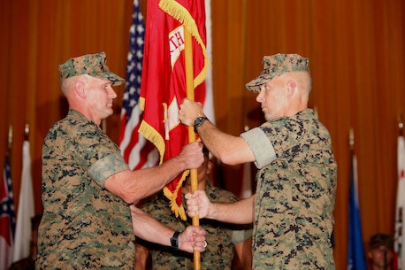 Col. David L. Odom, right, passes the 4th Marine Regiment colors to Col. Kevin A. Norton, left, June 16 at the theater on Camp Schwab.