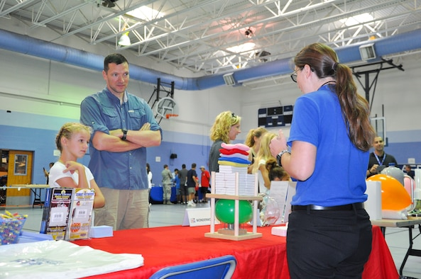Maj. John A. Carter, 45th Logistics Readiness Squadron commander, and his daughter Emma, 8, watch a Wonderworks demonstration during the 45th Space Wing's All SySTEMs Go event June 11, 2016, at the Youth Center/Shark Center at Patrick Air Force Base, Fla. The event was designed to teach children of all ages about science, technology, engineering and math. (U.S. Air Force Photo/Tech. Sgt. Erin Smith/Released)