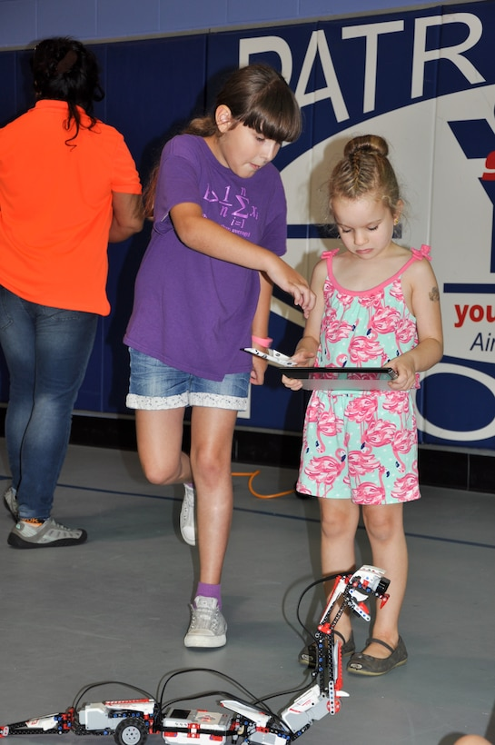 Annika, 8, shows Naylee, 5, how to control a snake built of Legos paired with software so that it would move similarly to a remote control car during the 45th Space Wing's All SySTEMs Go event June 11, 2016, at the Youth Center/Shark Center at Patrick Air Force Base, Fla. Annika built and programmed the snake herself, and used it to teach other children at the All SySTEMs Go event about science, technology, engineering and math. (U.S. Air Force Photo/Tech. Sgt. Erin Smith/Released)