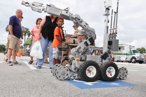 Staff Sgt. Amanda Ponce, 45th Civil Engineer Squadron Explosive Ordnance Disposal technician, teaches Josiah, 6, about the EOD's F-6 Alpha reconnaissance robot during the 45th Space Wing's All SySTEMs Go event June 11, 2016, at the Youth Center/Shark Center at Patrick Air Force Base. The robot is used by EOD members to neutralize explosives. (U.S. Air Force Photo/Tech. Sgt. Erin Smith/Released)