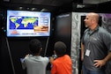 Joel Pickering teaches children about the importance of math as they play a video game created by student computer programmers from Full Sail University during the 45th Space Wing's All SySTEMs Go event June 11, 2016, at the Youth Center/Shark Center at Patrick Air Force Base, Fla. The event was designed to teach children of all ages about science, technology, engineering and math. (U.S. Air Force Photo/Tech. Sgt. Erin Smith/Released)