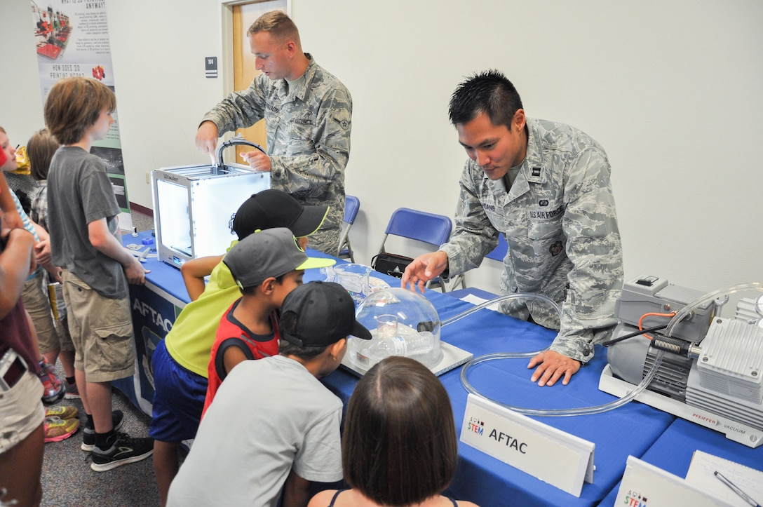 Airman Thomas Anastasio, left, a seismic analysist, and Capt. Jonathan Hoang, a chemist, both assigned to Air Force Technical Applications Center, teach children about science and how it ties to space during the 45th Space Wing's All SySTEMs Go event June 11, 2016, at the Youth Center/Shark Center at Patrick Air Force Base, Fla. The event was designed to teach children of all ages about science, technology, engineering and math. (U.S. Air Force Photo/Tech. Sgt. Erin Smith/Released)