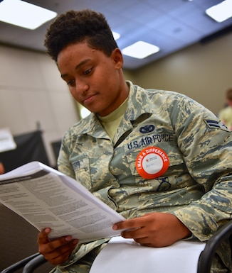 "Airman 1st. Class Ashlei Scott, 932nd Security Forces Squadron, looks over the information packet as the first step to donating blood with the American Red Cross, June 16, 2016 at the 932nd Airlift Wing building auditorium.  Scott, attending annual tour training at the 932nd, had no hesitations to donate blood and said this was her first time to donate.  ""I just want to give back, "" said Scott about her reason for donating.  (U.S. Air Force photo by Christopher Parr)"