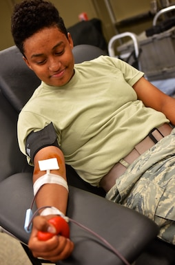 "Airman 1st. Class Ashlei Scott, 932nd Security Forces Squadron, slowly squeezes her fist as she watches the process of donating blood with the American Red Cross, June 16, 2016 at the 932nd Airlift Wing building auditorium.  Scott, attending annual tour training at the 932nd, had no hesitations to donate blood and said this was her first time to donate.  ""I just want to give back, "" said Scott about her reason for donating.  (U.S. Air Force photo by Christopher Parr)"