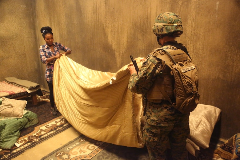A Marine with 2nd Civil Affairs Group helps a role player fold a blanket in a notional West African village during a training exercise that integrated 2nd CAG and II Marine Expeditionary Force Camp Lejeune, N.C., June 12, 2016. The training was designed to have the civil affairs specialists assess the damages and needs of villagers in a war-torn environment. (U.S. Marine Corps photo by Cpl. Joey Mendez/Released)