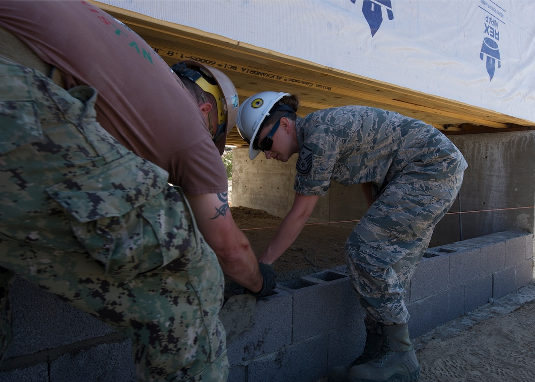 Builder 1st Class Carl Phillips, Naval Mobile Construction Battalion 22, teaches Master Sgt. Elizabeth Clark, 446th Civil Engineer Squadron 1st sergeant, how to set bricks for the foundation of a newly constructed house in Gallup, NM, June 13, 2016. Airmen and Navy Seabee's participated in Operation Footprint, a partnership of the Southwest Indian Foundation and the Department of Defense's Innovative Readiness Training program which provides an avenue for training military members .The two-week joint service training allowed members to construct homes which will be given to tribal members of the Navajo Nation who are in need. (U.S. Air Force Reserve photo by Tech. Sgt. Bryan Hull)