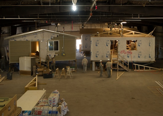 Citizen Airmen from the 446th Civil Engineer Squadron and Seabee's from the Naval Mobile Construction Battalion 22 construct houses in a warehouse in Gallup, NM, June 13, 2016. Reservists and Seabee's participated in Operation Footprint, a partnership of the Southwest Indian Foundation and the Department of Defense's Innovative Readiness Training program, which provides an avenue for training military members. The two-week training allowed joint service members to build homes, which will be given to tribal members of the Navajo Nation who are in need. (U.S. Air Force Reserve photo by Tech. Sgt. Bryan Hull)