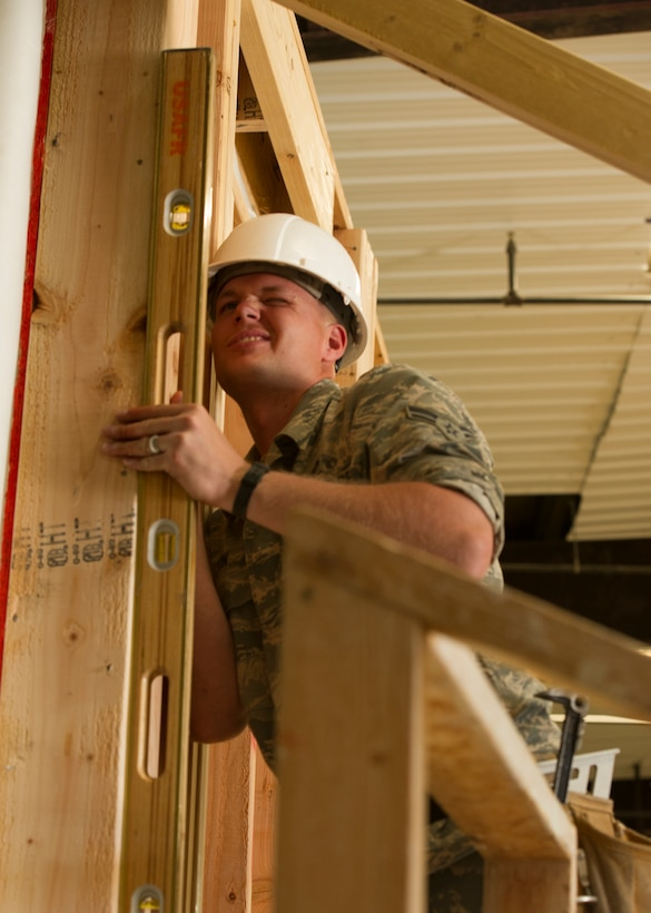 Airman 1st Class Rick Lyons, a utilities technician assigned to the 446th Civil Engineer Squadron, ensures that a wall of a house under construction is straight in Gallup, NM, June 13, 2016. Rainier Wing Citizen Airmen participated in Operation Footprint, a partnership of the Southwest Indian Foundation and the Department of Defense's Innovative Readiness Training program, which provides an avenue for training military members. Airmen teamed up with Seabee's from the Naval Mobilization Construction Battalion 22 to construct homes during their two weeks of annual training. (U.S. Air Force Reserve photo by Tech. Sgt. Bryan Hull)