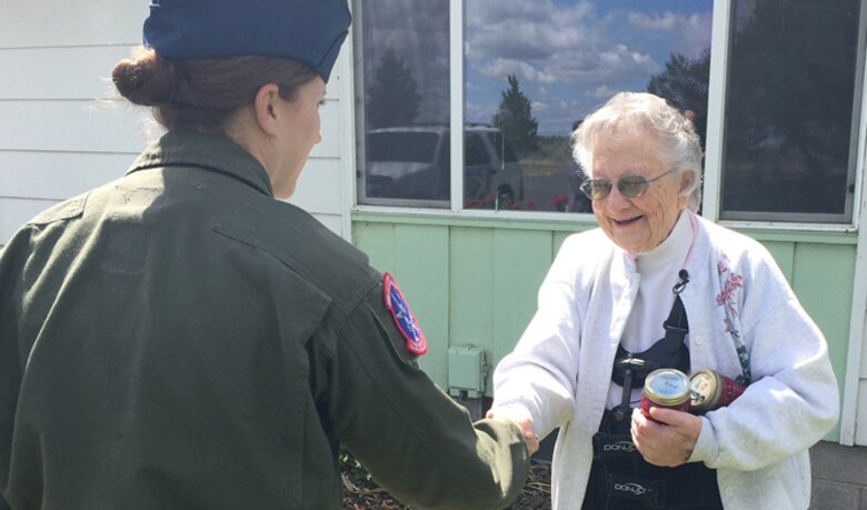 Tech. Sgt. Evangeline Evanzia, 93rd Air Refueling Squadron instructor boom operator, and Krem 2 News surprised Warden, Wash. native, Pat Rogers, to thank her for her contributions to the Treats 2 Troops program June 14, 2016. Since the start of the program 2011, Treats 2 Troops has sent more than 1,500 care packages to Fairchild Airmen serving overseas.(U.S. Air Force photo/Airman 1st Class Mackenzie Richardson)