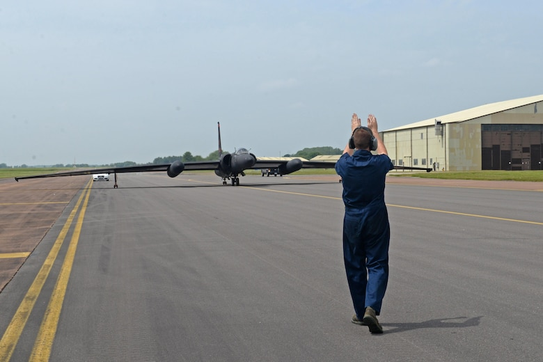 Staff Sgt. Jason Creese, 9the Aircraft Maintenance Squadron U-2 Dragon Lady dedicated crew chief, guides a U-2 Dragon Lady to park June 7, 2016, at Royal Air Force Fairford, Gloucestershire, England. The jet was met by an en route recovery team (ERT) in England to transition aircraft from and to Beale Air Force Base, California, and forward operating locations (FOL). The ERT is used like a pit crew at the midway point in Fairford, ensuring the aircraft are prepared to make it to their next destination. (U.S. Air Force photo by Senior Airman Ramon A. Adelan)