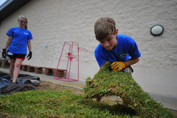 A child with Hurlburt Field's Special Operations Youth Group grabs a block of sod outside the Child Development Center East at Hurlburt Field, Fla., June 16, 2016. The youth group raised a $15,000 budget, which funded a wide range of projects, both on- and off-base. (U.S. Air Force photo by Airman 1st Class Joseph Pick)