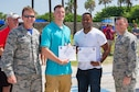 Brig. Gen. Wayne Monteith, 45th Space Wing commander; and Chief Master Sgt. Jason Lamoureux, 45th SW command chief, (far right) congratulate Airman 1st Class Nicholas McGaughey and Airman 1st Class Christopher Thornton, on their Below-the-Zone promotion during the Junior Enlisted Appreciation Picnic June 17, 2016, at Patrick Air Force Base, Fla. Below-the-Zone is a competitive early promotion program offered to enlisted U.S. Air Force personnel in the grade of Airman 1st Class/E-3. This early promotion opportunity is restricted to elite Airmen who stand out from their peers and perform duties at a level above their current rank. (U.S. Air Force photo/Matthew S. Jurgens/Released)