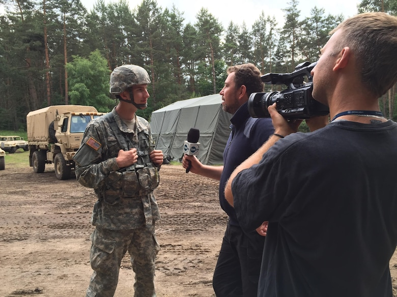 U.S. Army Reserve Pfc. James Hale, a Transportation Management Coordinator with the 3882nd Combat Sustainment Support Battalion, Joint Base Lewis-McChord, Washington, is interviewed by a Polish television reporter during Exercise Anakonda 2016 at the Drawsko Pomorskie Training Area, Poland, June 14. Hale, the son of American missionaries, was born in Poland and has lived most of his life there. He has served as a Polish translator for the soldiers in his unit during their time in Poland. Exercise Anakonda 2016 is a Polish-led, joint multinational exercise taking place throughout Poland June 7-17. The exercise involves approximately 31,000 participants from more than 20 nations. Exercise Anakonda 2016 is a premier training event for U.S. Army Europe and participating nations and demonstrates the United States and partner nations can effectively unite under a unified command while training on contemporary scenario. (U.S. Army photo by Timothy L. Hale) (Released)