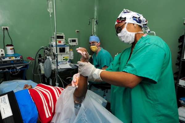 Capt. Lauren Quirao, 506th Expeditionary Medical Operations operating room nurse, cleans Espinal Ledi's arm in preparation for a bi-lateral carpal tunnel release surgery June 8, at Rio San Juan hospital, Dominican Republic.  Quirao is part of the tenth and final Medical Readiness Training Exercise or MEDRETE rotation during Exercise NEW HORIZONS 2016. Quirao is deployed from the 59th Medical Wing, Joint Base San Antonio, Texas. (U.S. Air Force photo by Master Sgt. Chenzira Mallory/released)