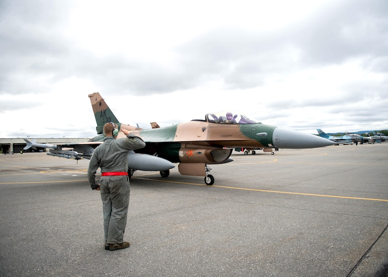 A U.S. Air Force crew chief with the 354th Aircraft Maintenance Squadron salutes Maj. Brian Bragg, the 18th Aggressor Squadron (AGRS) assistant director of operations, prior to the pilot's take off in a F-16 Fighting Falcon fighter aircraft for a sortie June 14, 2016, during RED FLAG-Alaska (RF-A) 16-2 at Eielson Air Force Base, Alaska. The 18th AGRS participation in RF-A and similar exercises signifies continued commitment to peace, stability and alignment in the Indo-Asia-Pacific region. (U.S. Air Force photo by Staff Sgt. Shawn Nickel/Released)