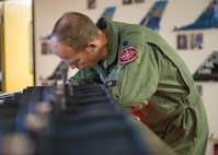 """U.S. Air Force Lt. Col. Micah Bell, the 354th Operations Support Squadron commander, fills out flight paperwork at the 18th Aggressor Squadron operations desk prior to a a sortie June 14, 2016, during RED FLAG-Alaska (RF-A) 16-2 at Eielson Air Force Base, Alaska. Pilots from Eielson take on the role of Red Air """"bad guys"""" during large scale exercises and train Blue Air pilots during RF-A. (U.S. Air Force photo by Staff Sgt. Shawn Nickel/Released)"""