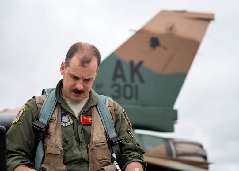 "U.S. Air Force Maj. Brian Bragg, the 18th Aggressor Squadron assistant director of operations, reads maintenance continuity reports prior to take off as a ""bad guy"" for a sortie June 14, 2016, during RED FLAG-Alaska (RF-A) 16-2 at Eielson Air Force Base, Alaska. RF-A, a U.S. Pacific Air Forces commander-directed exercise, has helped train more than 150,000 aircrew members for combat in the past 40 years. (U.S. Air Force photo by Staff Sgt. Shawn Nickel/Released)"