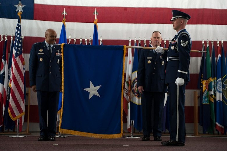 New Brig. Gen. Michael Lutton, who is headed to the Pentagon to work with the Department of Energy, is presented his Brig. Gen. flag by Tech. Sgt. Joshua Hull, non-commissioned officer in charge of Base Honor Guard, at Minot Air Force Base, N.D., June 17, 2016. The presentation of the General flag is an Air Force tradition. (U.S. Air Force photo/Senior Airman Kristoffer Kaubisch)