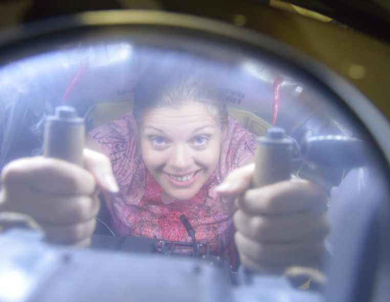 Angela Woolen, Robins Rev-Up staff writer, shows how tight the quarters were for the B-17 ball turret gunner. (U.S. Air Force photo by Ray Crayton)
