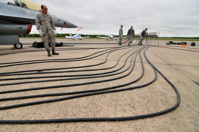 U.S. Air Force Staff Sgt. Matt Wagner, left, aircraft maintainer with the New Jersey Air National Guard's 177th Fighter Wing, surveys pneumatic hoses connected to a lifting bag assembly under a decommissioned F-16D Fighting Falcon during Crash Damaged Disabled Aircraft Recovery (CDDAR) training at the Naval Air Station Wildwood Aviation Museum in Cape May, N.J. May 22, 2016. The 177th CDDAR team consists of personnel from the engine, electrical-environmental, weapons, hydraulics and egress shops, as well as crew chiefs, who are selected for the additional duty based on expertise in their field. (U.S. Air National Guard photo by Master Sgt. Andrew J. Moseley/Released)