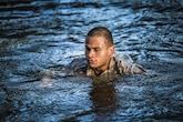 A Marine swims out of the water after falling from a rope obstacle at a confidence course in Marine Corps Recruit Depot Parris Island during a physical training event June 9. The Provost Marshal's Office coordinated the event to challenge the Marines physically, build camaraderie and promote teamwork. Marines from every section of PMO participated in the event. The Marine is with PMO, Marine Corps Air Station Beaufort.