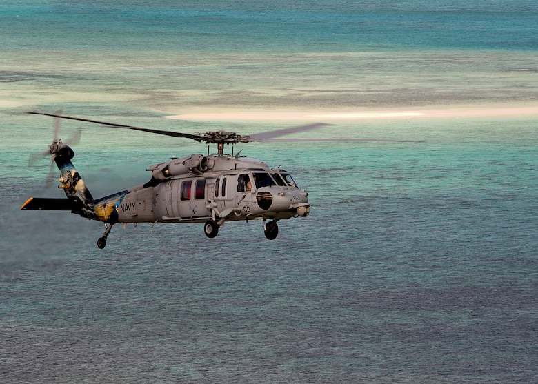 An MH-60S Sea Hawk helicopter assigned to the Island Knights of Helicopter Sea Combat Squadron (HSC) 25 is pictured during a photo exercise off the coast of Guam. HSC-25 maintains a 24-hour search and rescue and medical evacuation alert posture, directly supporting the U.S. Coast Guard, Sector Guam and Joint Region Marianas. HSC-25 ensures maritime peace and security in the U.S. 7th Fleet area of responsibility. (U.S. Navy photo by Chief Mass Communication Specialist Joan E. Jennings/Released)