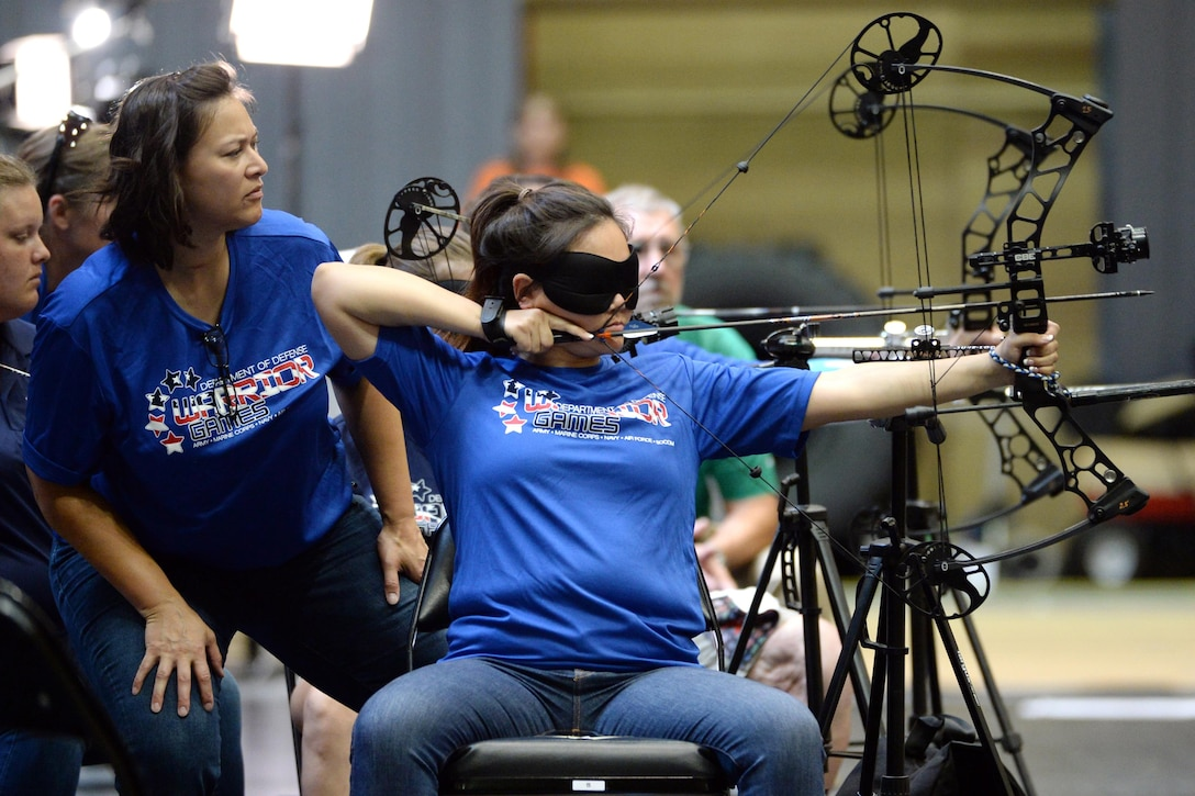 Air Force Master Sgt. Zarah Hartsock helps Air Force 1st Lt. Sarah M. Frankosky line up a shot during an archery competition for the visually impaired at the 2016 Department of Defense Warrior Games at the U.S. Military Academy in West Point, N.Y. June 17, 2016. Sound devices also help the archers aim at the targets. DoD photo by EJ Hersom